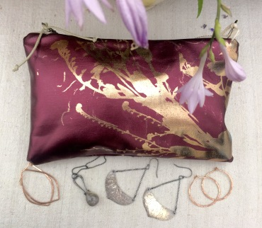 A rose gold bag from Planetarium design by Esther Yaloz with rose gold hoops oxidized silver pieces.